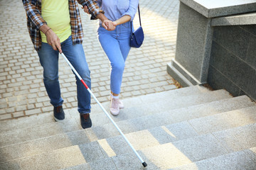 Blind mature man with his daughter walking outdoors