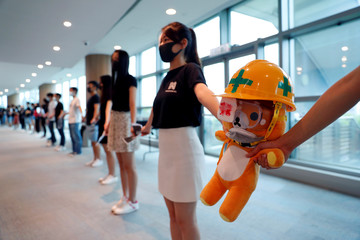 Medical students hold a stuffed doll with its eye covered as they form a human chain during a protest against the police brutality at the Faculty of Medicine in The University of Hong Kong