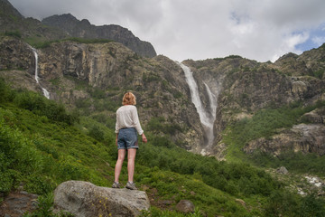 Woman standing on the rock and enjoying the view of epic waterfall