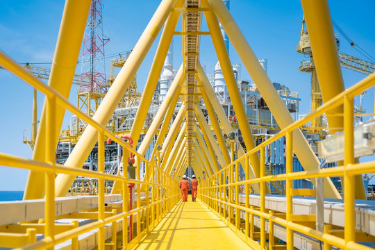 Worker walking at the connection bridge between quarter platform and oil and gas central processing platform, offshore oil and gas operation business.
