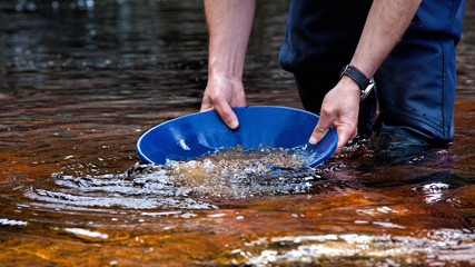 Man in a dry suit gold panning in the Kildonan Burn for gold