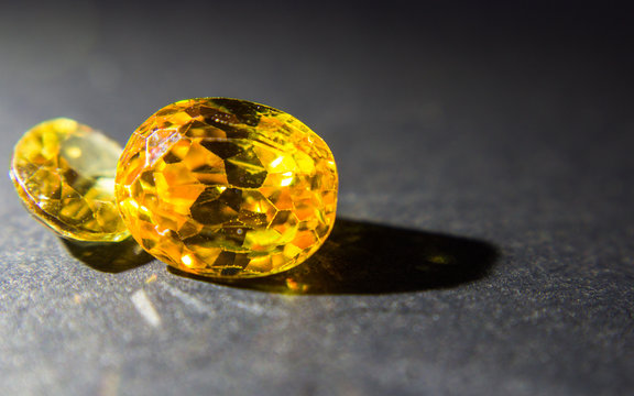 Natural yellow Sapphire gemstone, beautiful yellow gold citrin gemstone isolated on black background, as jewelry background