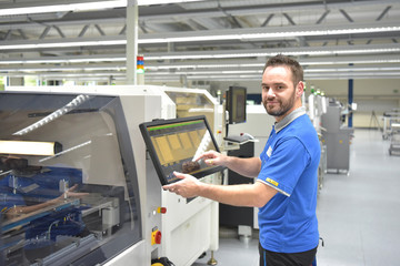 Arbeiter in einer modernen Fabrik bedient Maschine - Portrait Mann am Arbeitsplatz