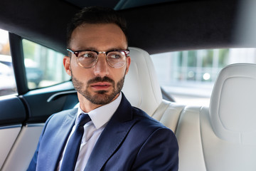 Dark-eyed bearded businessman sitting on back seat in car