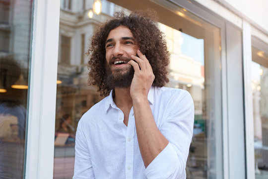 Happy curly bearded guy walking down street and having pleasant talk on his phone, looking ahead and smiling widely, wearing white shirt