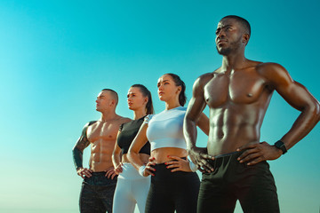Group of four young sportsmens women and men, fit athletes are standing on the sky background...