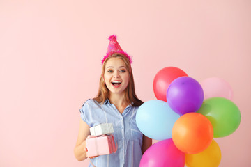 Happy woman with gifts and Birthday balloons on color background