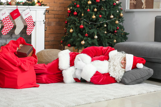 Tired Santa Claus sleeping on floor in room decorated for Christmas