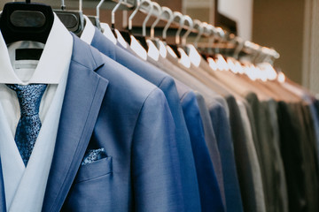 Men suit jackets on hanger in a shop Fotobehang