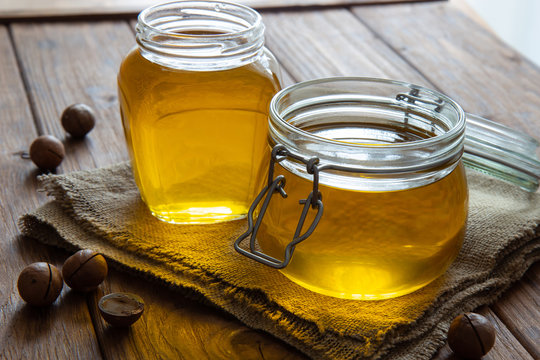 Two jars of clarified ghee butter on a wooden table.