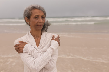 Senior woman with arms crossed standing on the beach