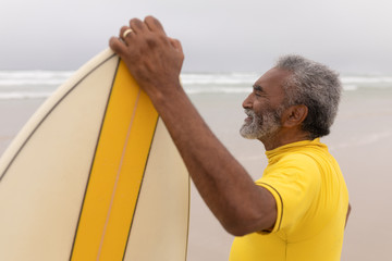 Senior male surfer standing with surfboard on the beach