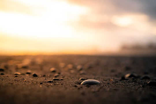 Dramatic sunset over a black sand beach with pebbles, Bali, Indonesia