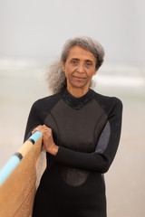 Senior female surfer standing with surfboard and looking at camera on the beach