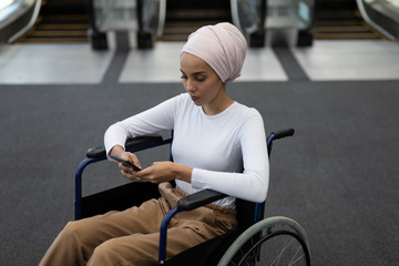 Young disabled mixed-race female executive using mobile phone in the lobby