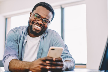 Cheerful african american hipster guy laughing at funny video on smartphone during free time, happy dark skinned man enjoying good connection of 4G internet for watching movie on mobile phone.