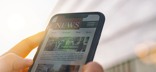 Online news article on smartphone screen. Electronic newspaper or magazine. Latest daily press and media. Mockup of digital portal and website. person using web service in the morning. Reading text.