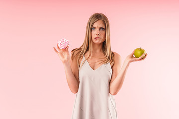 Image of perplexed blond woman wearing dress hesitating while holding sweet donut and green apple isolated over pink background in studio