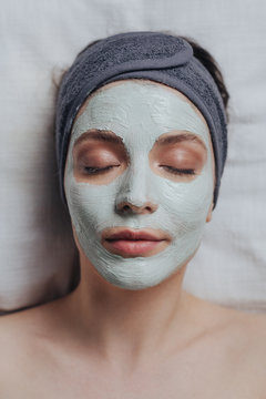 Portrait of pretty Caucasian woman laying at spa salon with cosmetic mask on her face.