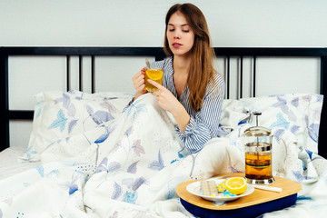 Young woman sitting on the bed with lots of medicine on the bed table.