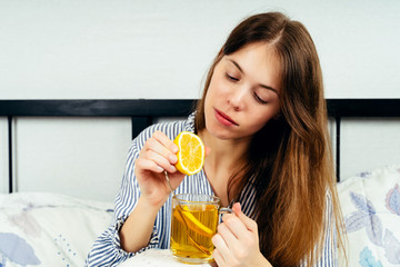 Young woman sitting alone on the bed with a cup of tea