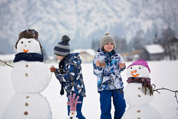 Family with children, building snowman in the park in little village in Austria