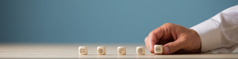 Hand of a businessman placing wooden cubes with contact, communication and location icons