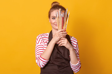 Horizontal shot of girl artist holds brushes in hands and hides behind it, lady dresses stripes casual shirt and brown apron, blonde woman with bunch, posing isolated over yellow studio background. Wall mural