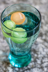 Blue green Cola glass with colored round ice cubes on gray stone platform.  High angle view.