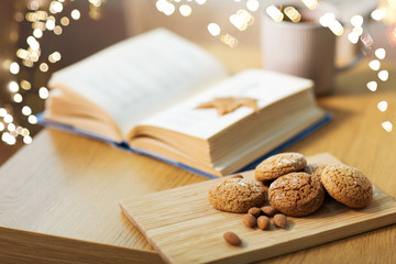 Fototapete - hygge, bake and food concept - oatmeal cookies, almonds, book and tea on wooden table at home