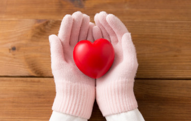 Photo sur Aluminium Graffiti collage winter, valentine's day and christmas concept - hands in pale pink woollen gloves holding red heart over wooden boards background