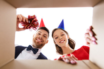 people, surprise and holidays concept - happy couple in party hats opening birthday gift box