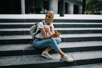 Smiling hipster girl resting on stairs enjoying eating street food on lunch,happy female traveler tasting snack and drinking ice coffee sitting on urban settings having break during walking trip .