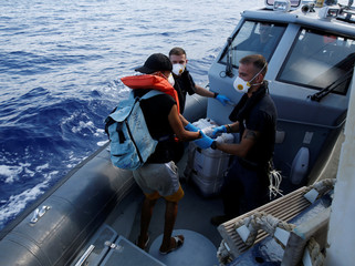 An ill Tunisian migrant is assisted by Armed Forces of Malta sailors during his medical evacuation to Malta from the German NGO Sea-Eye migrant rescue ship 'Alan Kurdi' in international waters off Malta in the central Mediterranean Sea