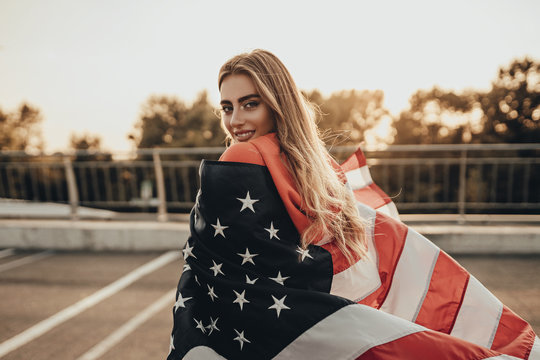 Beauty portrait of active happy girl with american flag on road near parking in summer sunset in evening. Stylish urban woman model posing in red hoodie
