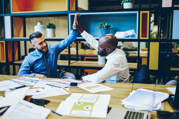 Smiling multiracial male colleague celebrating achievement in business development overjoyed in office,happy partners giving high five after completed cooperation working process on successful project