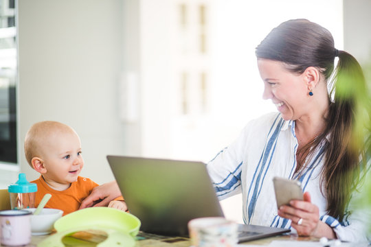 Cheerful businesswoman playing with daughter while running business from home office