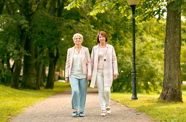 old age, retirement and people concept - two senior women or friends walking along summer park Wall mural
