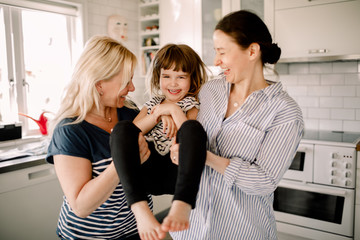 Mothers holding smiling daughter while standing in kitchen