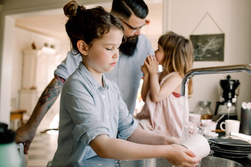 Girl washing mug at sink while father talking to daughter in kitchen