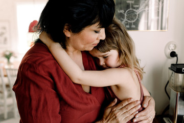Caring mother holding sad daughter while standing at home