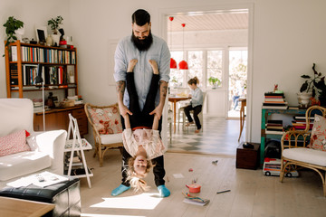 Playful father swinging girl while standing in living room at home