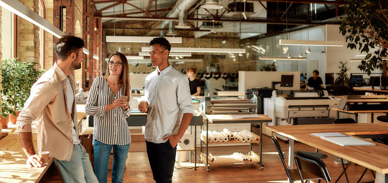 Nice talk. Three young colleagues in casual wear holding coffee cups and discussing something while standing in the modern office. Coffee break. Web banner