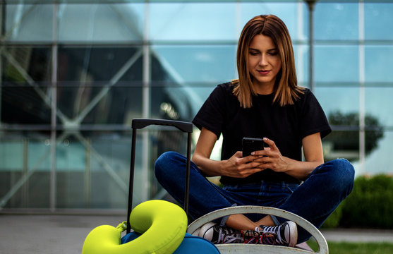 A girl with a suitcase and travel pillow on the bench near the airport is looking at smartphone waiting for flight.