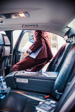Businessman getting out from the limo with lap top