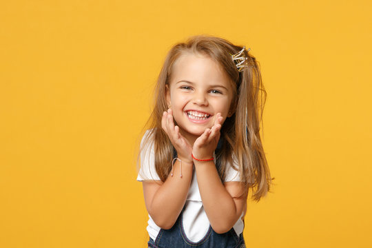 Little cute child kid baby girl 4-5 years old wearing light denim clothes isolated on pastel yellow wall background, children studio portrait. Mother's Day, love family, parenthood childhood concept.