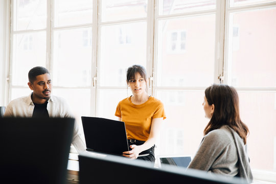 Female software engineer explaining to coworkers while sitting against window in office