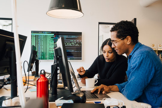 Focused male and female engineers coding over laptop on desk in office