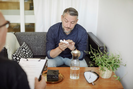 Sad mature man with tissue sharing problems during therapy session