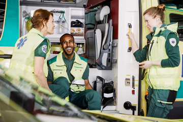 Happy multi-ethnic paramedics talking while sitting in ambulance at parking lot